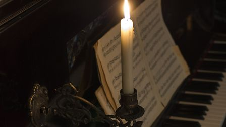 Close-up of a burning candle on the piano.