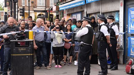 A crowd gathers behind a police cordon on Barking Road in East Ham (Picture: Stefan Rousseau/PA Wire