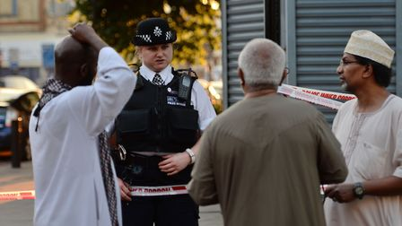 A police officer talks to local people at Finsbury Park in north London, where one man has died, eig