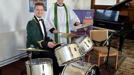 The bands drummer Simon Warren practicing for the concert in Pakefield Church helped by Canon Baker.