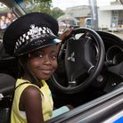 Sainabou Cham, five, playing in a police car at Our Community Festival