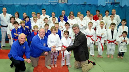 Lowestoft Lions president Michael Cook presents a cheque towards the cost of new mats to Iceni Judo