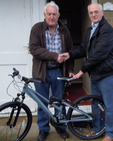 The second photograph shows Rotarian Barry Scaplehorn presenting the mountain bike to the winner, Mr