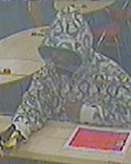 Marcus Moore with a gun inside one of the betting shops (Picture: Met Police)