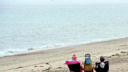 A couple sunbathe on the beach as they enjoy the sunny weather at Clacton-on-Sea in Essex. Clacton f