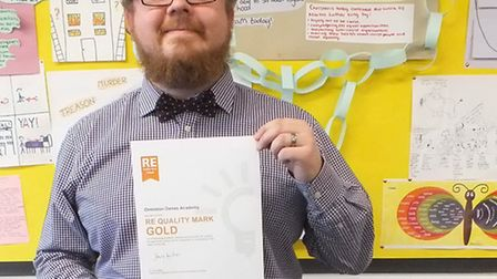 Mr Wayne Buisst, Head of RE at Ormiston Denes, holding the RE Quality Mark certificate