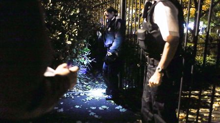 The police officers find condoms and bedding behind a bush on the side of the road where an arrest w