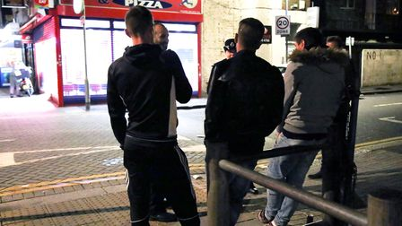 Police officers speak to three young men who have been drinking and are standing on a street corner,