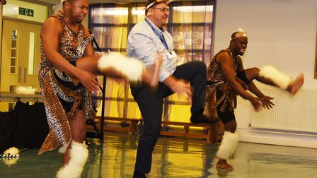 African tribal dance performers entertaining children at Avanti Court School with a teacher joining
