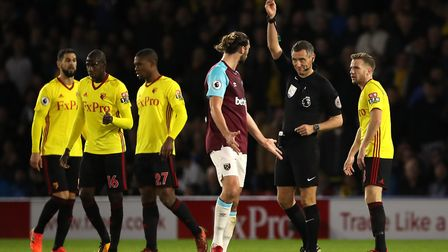 Match referee Andre Marriner (second right) books West Ham United's Andy Carroll (centre) during the