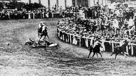 Suffragette Emily Davison lies on the ground after attempting to grab hold of the King George V hors