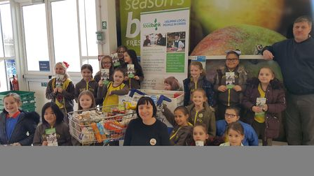 Mark Reeves from Harold Hill Foodbank, Clover Deacon from Tesco and the 4th Harold Wood Brownies wit