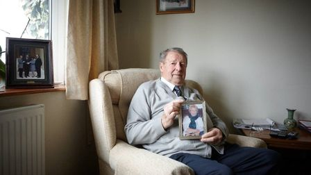 Leonard with a picture of his wife Annette, who died from cancer that she contracted from washing hi