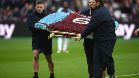 A floral tribute is taken onto the pitch to commemorate the 25th anniversary of the passing of Bobby