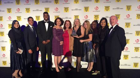 Haven House staff collect a trophy for being ranked one of the top 100 employers among UK non-profit