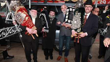 Rabbi Sufrin MBE with members of Chabad Community holding chabad torah scroll outside new centre rec