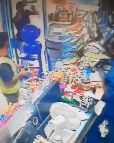 A gang member throw boxes and bags at the shop owner