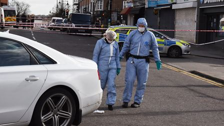 Police and forensic officers at the scene of the stabbing on Snakes Lane East Woodford Green outside