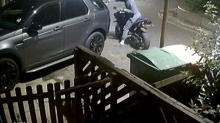 CCTV footage shows a motorcyclist dressed in grey approach the car and throw something into the back