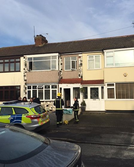 Police and a firefighter outside the property in Laburnum Avenue, Hornchurch investigate the cause o