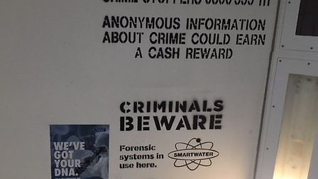 Information on Crimestoppers, the anonymous reporting service, written on the ceiling of the cell. P