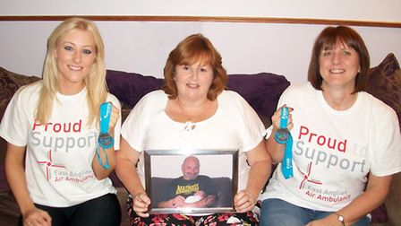 Stacey Ellis, Cathy House and Lizzie Ellis with a picture of Neil House and their medals.