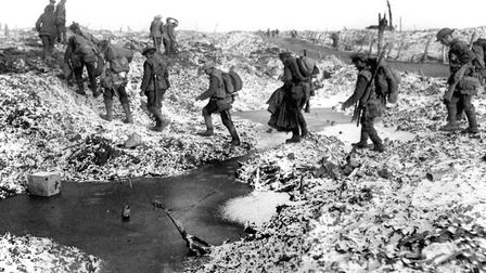 British soldiers negotiating a shell-cratered, Winter landscape along the River Somme in late 1916 a