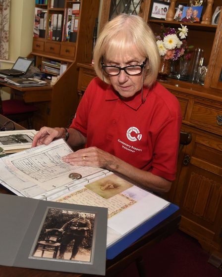 Patricia Barber looking at pictures and information on her Grandfather.