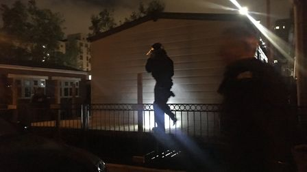 An officer storming a property in Parkway Crescent, Stratford, where one suspect was arrested. Pictu