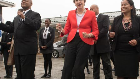 Prime minister Theresa May dancing with students and staff at ID Mkize Secondary School in Cape Town