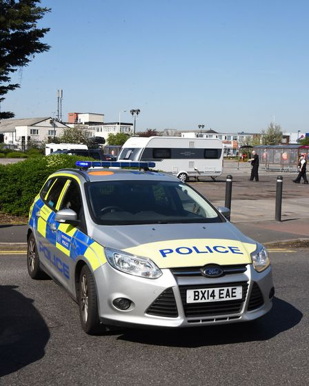 Police at the car park where travellers have forced the closure of Tesco at Gallows Corner