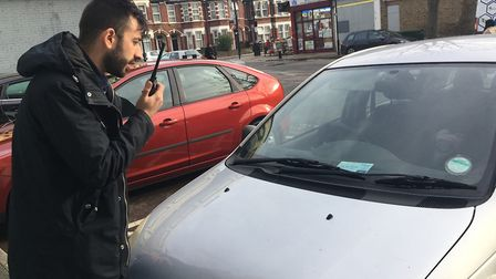 Law enforcement officer Andrew Boot, checking if a blue badge isn't expired or registered stolen. Pi