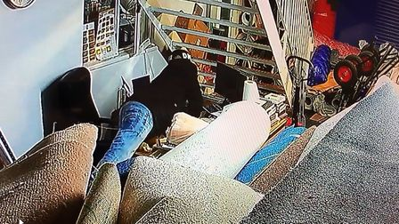 CCTV shows a supposed customers reaching over the counter of Taj Carpets, in Hickling Road. Photo: T