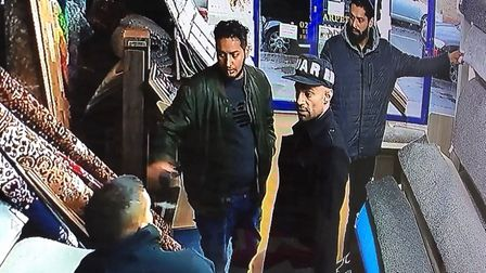 Three alleged accomplices who reported stole £300 from Taj Carpets speak with a shop keeper. Photo:
