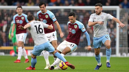 Burnley's Dwight McNeil (centre) and West Ham United's Mark Noble (left) battle for the ball during