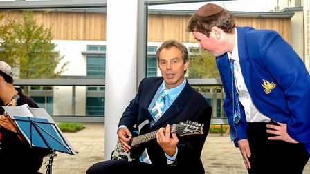 Former prime minister Tony Blair plays guitar in a 2002 visit to the Jewish Free School, Harrow. Pho