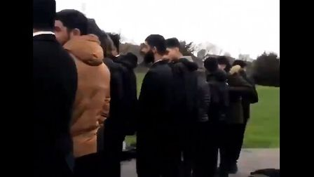 A still from a clip posted on Twitter showing a number of Muslim students praying outside in the pla