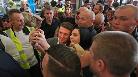 Tommy Robinson (centre) surrounded by supporters at City Thameslink railway station. Photograph: Yui