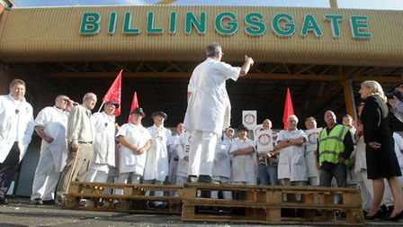 Workers stand outside Billingsgate Market in London in a demonstration against planned changes to th