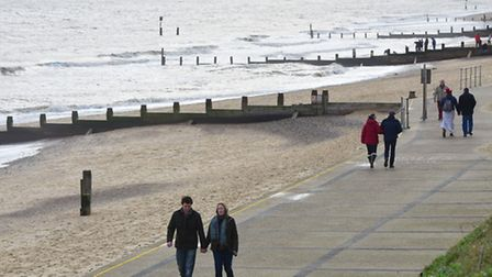 Walkers enjoying the mild December weather along Southwold seafront.