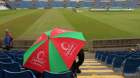 A spectator shelters under an umbrella as rain delays play during Yorkshire CCC vs Essex CCC, Specsa