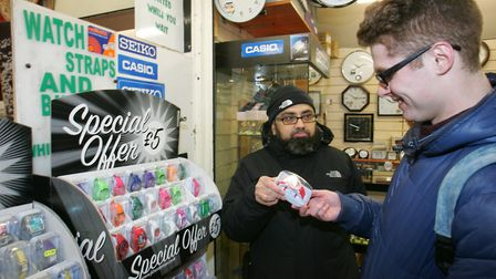 Trader Ibrahim Patel sells a watch to a customer. Picture: Steve Poston