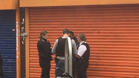 Police officers stop and search a man they believe was acting suspiciously in Romford town centre.
