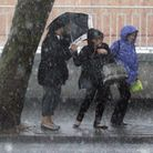 Three women shelter from a heavy rain and hail storm under a tree in London, on the first day of the