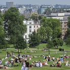 People enjoy the hot weekend weather and the views on north London's Primrose Hill.