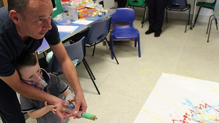 Alfie and his dad ejoying syringe painting during Play in Hospital Week. Picture: BHRUT