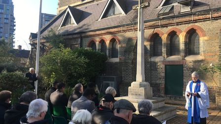Lay reader Carole Davison leads the Canning Town service of Remembrance at the St Luke's memorial. P