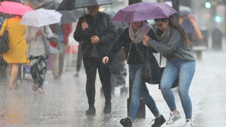 People caught in the rain in central London during last year's heatwave. Extreme weather could becom