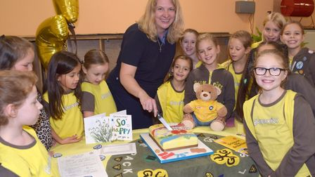 Sarah Wiles, unit leader and Brown Owl, cutting cake with the 1st Cranham Brownies. Picture: David H