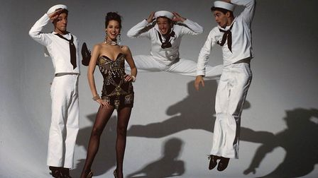 Model Christy Turlington in an embroidered black dress by Gianni Versace, amid sailors from Jerome R